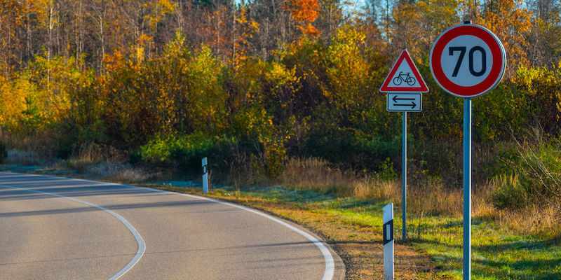 Unused road with speed limit 70 km/h signs, in the background a beautiful autumn forest in sunlight.