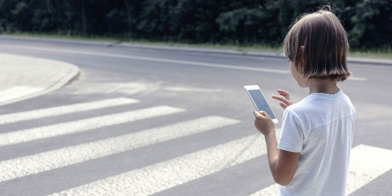 A Small Child Crossing at the Pedestrian Crossing While Looking at His Phone